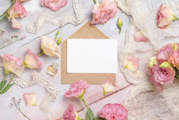 Rosa blumen und eine leere grußkarte mit umschlag auf einem marmortisch, der mit vintage-bändern verziert ist
