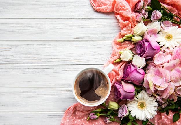 Rosa blumen und tasse kaffee auf einem weißen hölzernen hintergrund