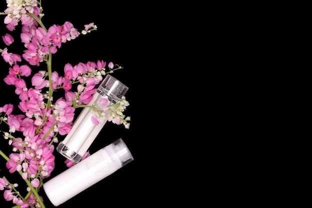 Rosa blumenbergsteiger mit shampoo- und conditionerflaschen