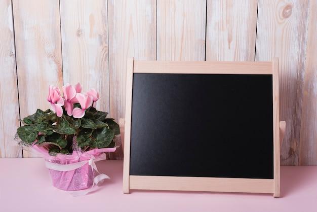 Rosa blumenblumenstrauß mit kleiner leerer tafel auf schreibtisch gegen hölzerne wand