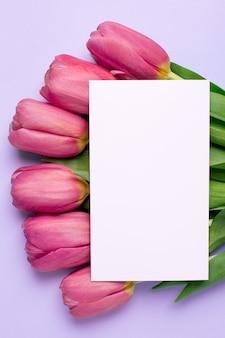 Rosa blumentulpen und geschenkkarte auf einer lila oberfläche
