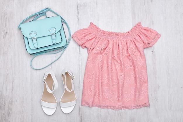 Rosa bluse, weiße schuhe und handtasche. modisches konzept. oberfläche aus holz.