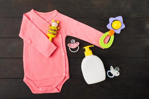 Rosa bodusuit, der zwei rasseln und zwei sylikonschnuller mit babyseife auf braunem holztisch hält
