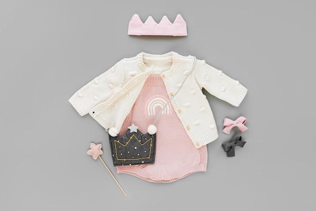 Rosa body mit strickpullover, kinderhandtasche, baumwollkrone und zauberstab. set babykleidung und zubehör auf grauem hintergrund. mode kinder outfit. flache lage, ansicht von oben