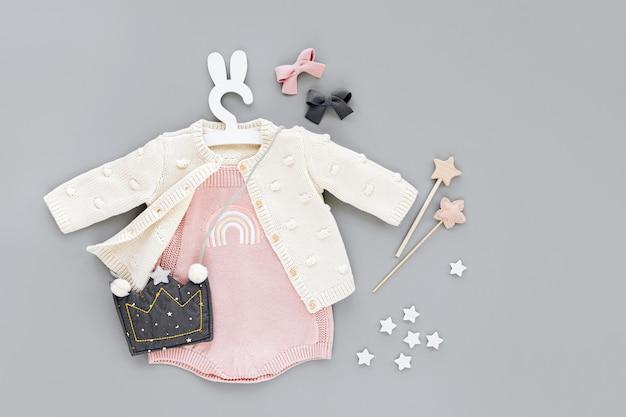 Rosa body mit strickpullover, kinderhandtaschenform der krone auf süßem kleiderbügel mit hasenohren. set babykleidung und zubehör auf grauem hintergrund. mode kinder outfit. flache lage, ansicht von oben