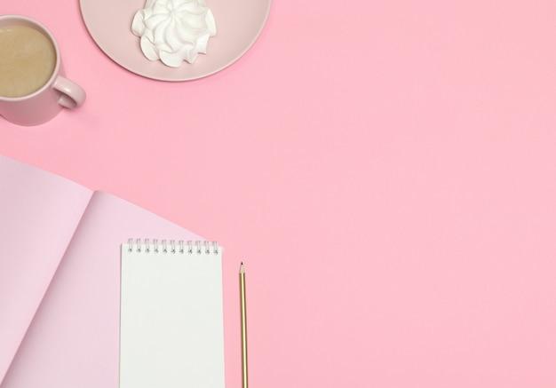 Rosa briefpapier, kaffeetasse, kuchen auf rosa hintergrund