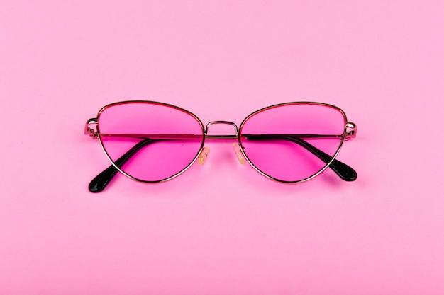 Rosa brille auf einem rosa raum. glamour und stil. brille für frauen. die wohnung lag. ein ort zum schreiben. werbestudio schoss von rosa brille.