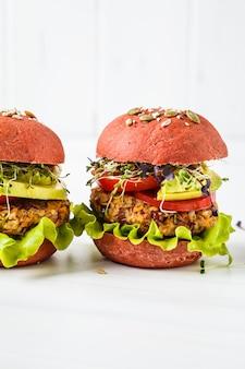 Rosa burger des strengen vegetariers mit bohnenkotelett, -avocado und -sprösslingen auf weiß