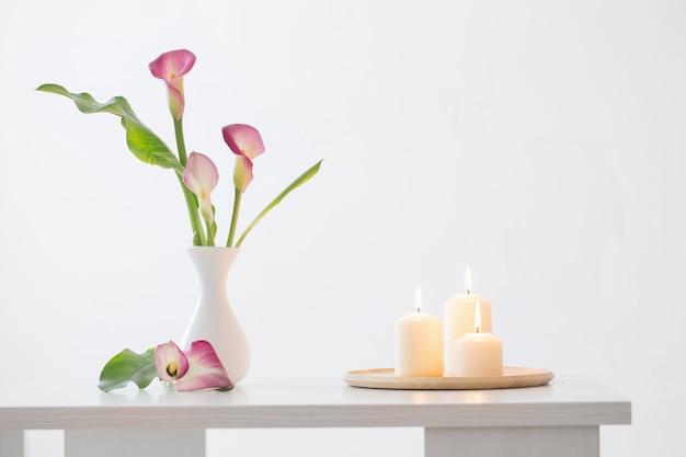 Rosa callalilie in der vase und brennende kerzen auf weißer oberfläche