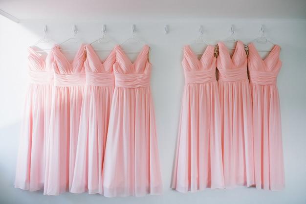 Rosa chiffonkleider der identischen brautjungfern auf kleiderbügeln in reihe
