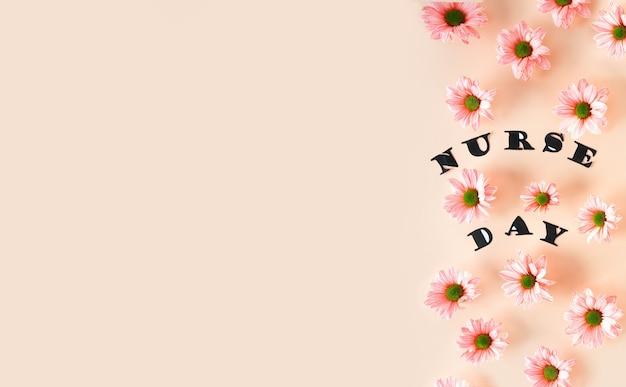 Rosa chrysanthemen auf pastellrosa hintergrund und stilvolle buchstaben-draufsicht mit kopienraum floral