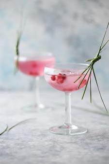 Rosa cocktail hautnah. getränk mit rosen- und prosecco in trinkgeschirr. exotische französische cocktailportion mit crushed ice in glaswaren