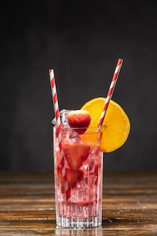 Rosa cocktail mit eis und erdbeeren, verziert mit orangenscheibe