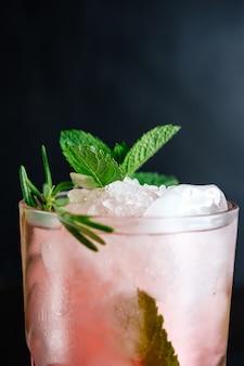 Rosa cocktail mit minze und rosmarin auf schwarzer nahaufnahme
