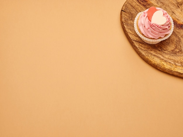 Rosa cupcakes kuchen mit herzen auf einem küchenholzbrett auf einem beige braunen hintergrund