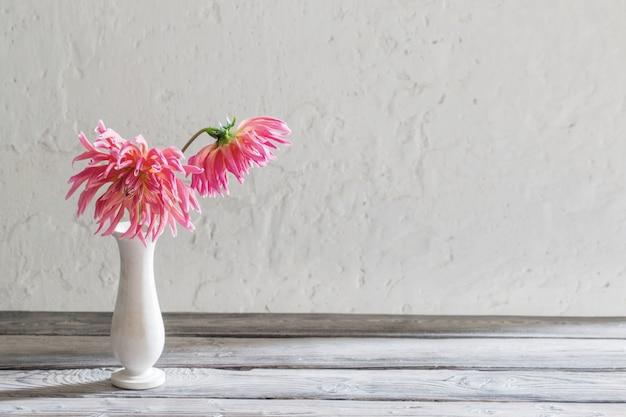 Rosa dahlie in der vase auf holztisch