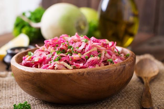 Rosa daikon-salat mit äpfeln, eingelegten zwiebeln und petersilie