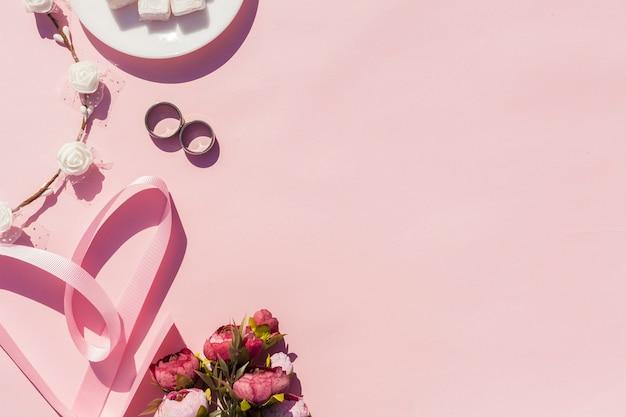 Rosa dekoration mit hochzeitseinzelteilen und kopienraum