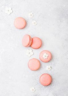 Rosa dessertkuchen macaron oder makrone mit weißen süßen blumen auf steinküche.