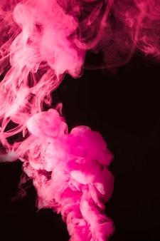 Rosa dichter rauch auf dem schwarzen hintergrund