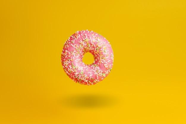Rosa donut auf gelb mit schatten