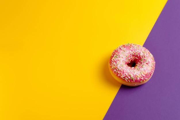 Rosa donut auf gelbem und violettem tiefpurpurnem draufsicht-kopienraum der wand