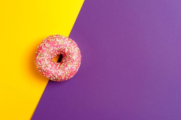 Rosa donut auf gelbem und violettem tiefviolettem hintergrundkopienraum der draufsicht