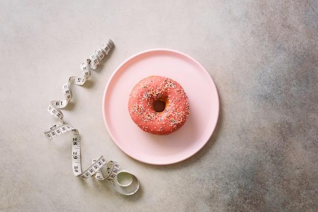 Rosa donut auf platte, messendes band über grauem konkretem hintergrund.
