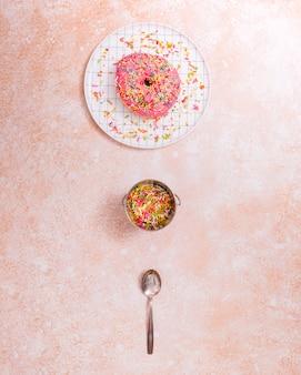 Rosa donut auf teller; streusel und löffel auf rustikalen strukturierten hintergrund