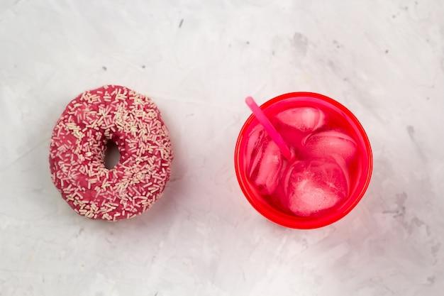 Rosa donut der draufsicht und kaltes getränk
