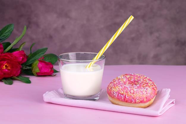 Rosa donut mit einem glas milch auf einem rosa tisch