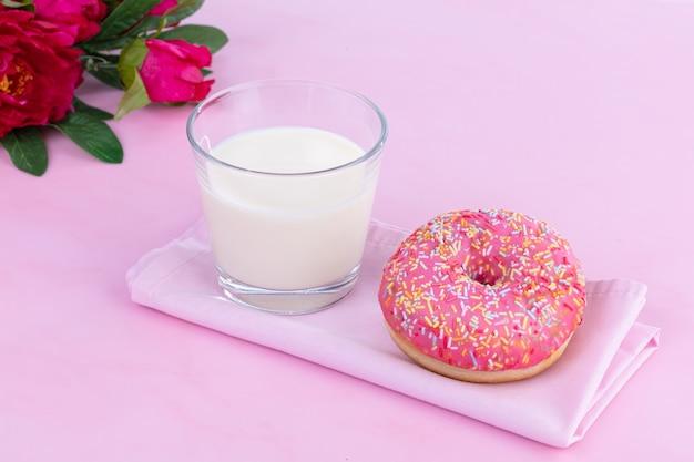 Rosa donut mit einem glas milch auf einer rosa oberfläche