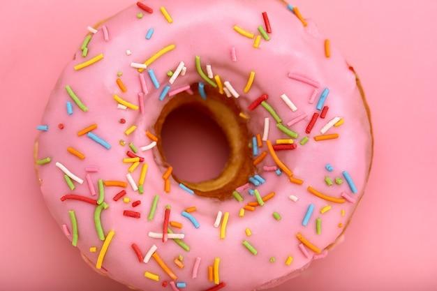 Rosa donut mit farbigen streuseln auf einer rosa oberfläche, nahaufnahme, konzept der desserts, konzept der rosa farbe auf rosa