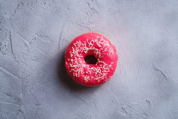 Rosa donut mit streuseln, süßes glasiertes dessertnahrungsmittel auf strukturiertem betonhintergrund, draufsicht