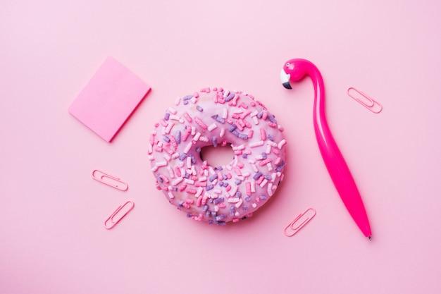 Rosa donut- und flamingostift auf rosa. draufsicht flach legen.