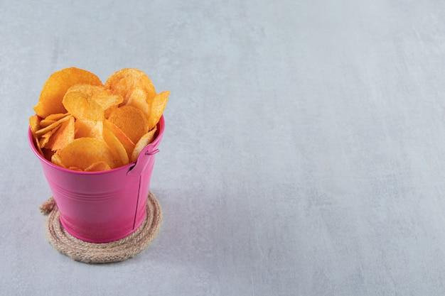 Rosa eimer mit würzigen chips auf stein gelegt.