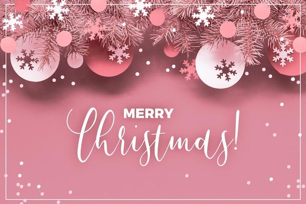 Rosa einfarbiges weihnachten mit den tannenzweigen und papierdekorationen - flitter und schneeflocken. modische flache lage, draufsicht, abgetöntes gefiltertes bild auf papier, text