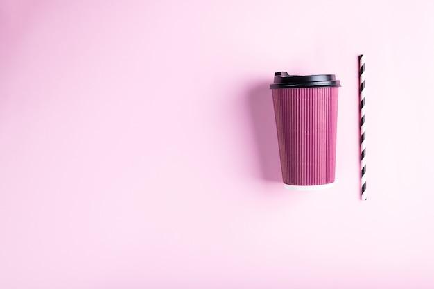 Rosa einweg-pappbecher mit gestreiftem papierstroh