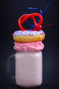 Rosa erdbeer-freakshake mit marshmallow und süßigkeiten.