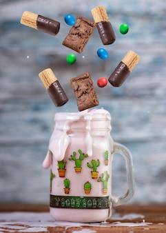 Rosa erdbeer-freakshake mit süßigkeiten in der luft, die herunterfallen