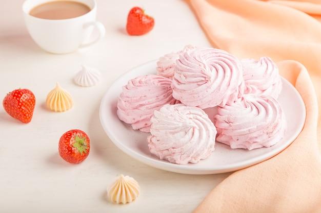 Rosa erdbeer hausgemachter zephyr oder marshmallow mit tasse kaffee auf weißer holzoberfläche mit orangefarbenem textil