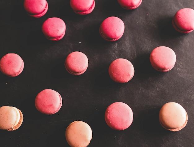Rosa erdbeer-macarons auf schwarzem hintergrund