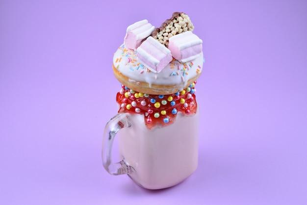 Rosa erdbeermilchshake mit marshmallow und süßigkeiten