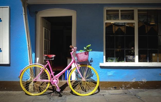 Rosa fahrrad mit gelben rädern vor einem blauen haus