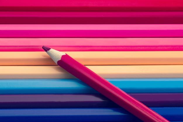Rosa farbbleistift auf vielen bunten bleistiften hintergrund, pastellfarben ton