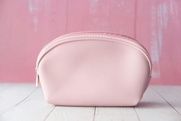Rosa farbe frauen lässige tasche auf holzhintergrund.