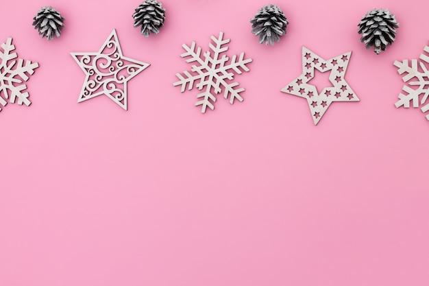 Rosa flacher laderahmen mit schneeflocken, weihnachtsspielzeug und zapfen.