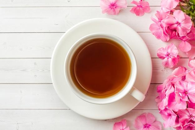 Rosa flammenblumen und ein tasse kaffee auf einer weißen tabelle.
