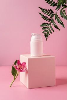 Rosa flasche mit feuchtigkeitscreme auf podium und pastellhintergrund. kosmetisches containermodell mit platz für text. natürliches beauty-produktkonzept für die hautpflege.
