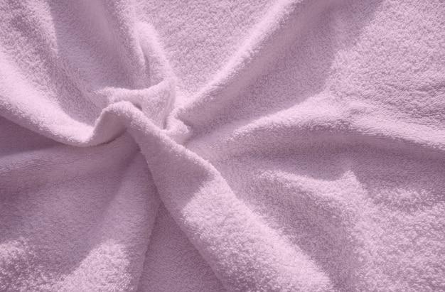 Rosa flauschiges frottiertuch, ein einfaches beispiel für die textur eines weichen, flauschigen stoffes, ein hintergrund aus falten